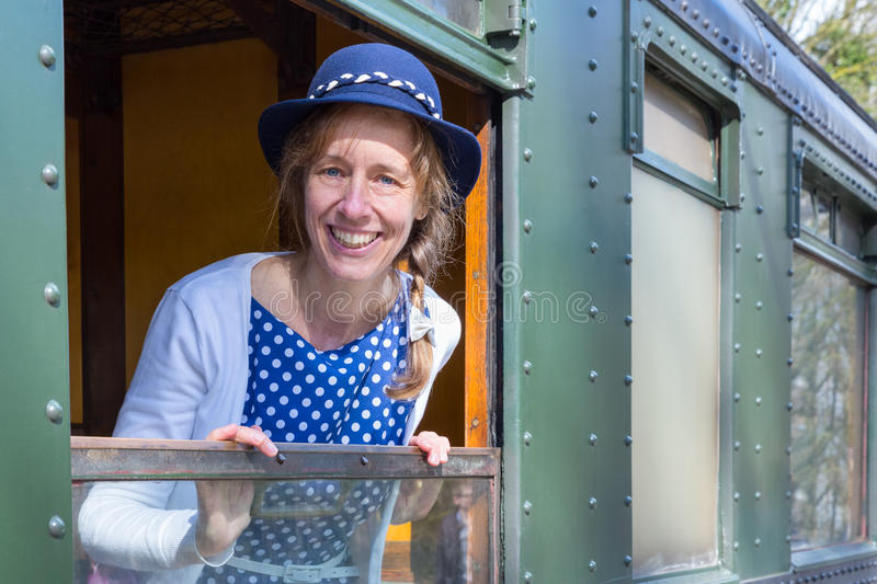 Woman in old-fashioned clothes in window of steam train. Caucasian woman in old-fashioned clothes in window of steam train. The dutch woman wears a blue dress stock photo