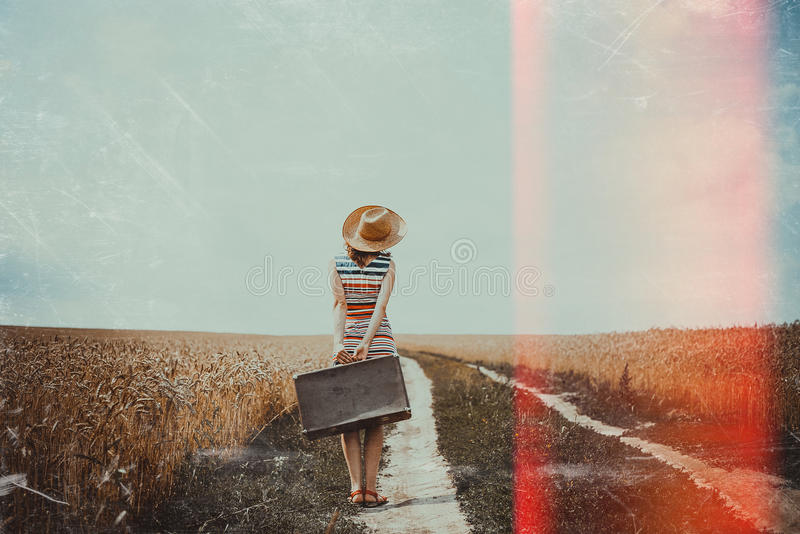 Woman with old suitcase standing on film light stock photo