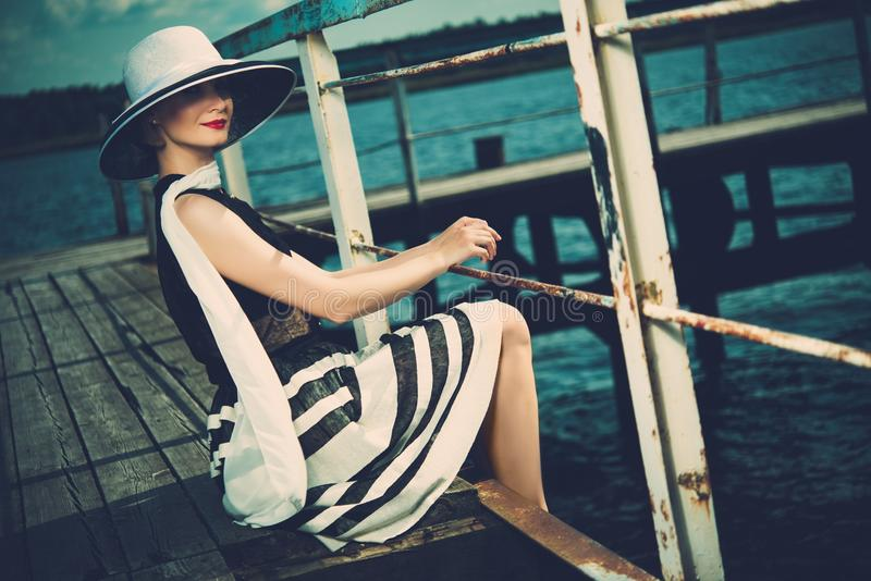 Woman on old wooden pier. Beautiful woman wearing hat and white scarf sitting on old wooden pier stock photos