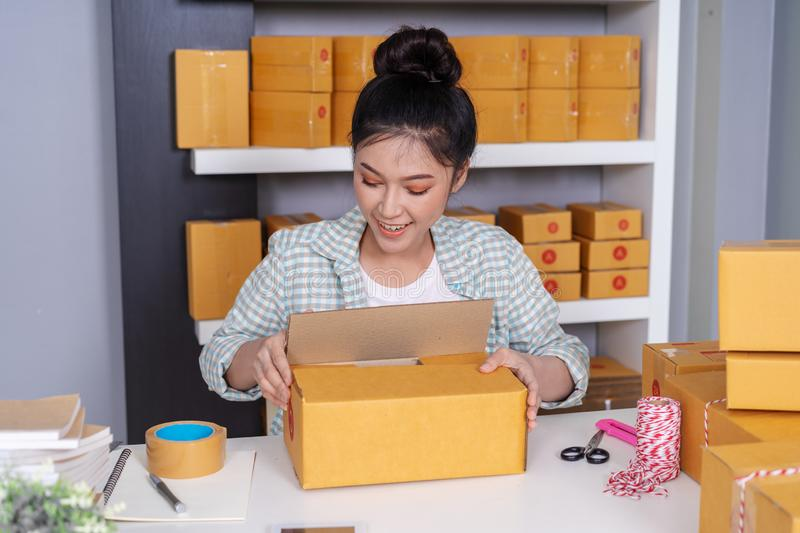 woman online entrepreneur packing parcel box at home office, prepare product for deliver to customer royalty free stock images