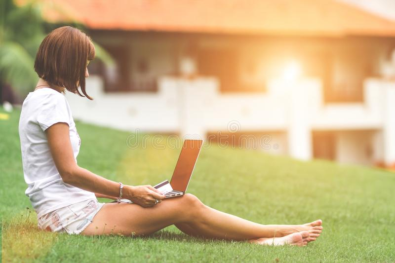 Woman online shopping concept. Woman in the green park with modern laptop. Bali island. stock images
