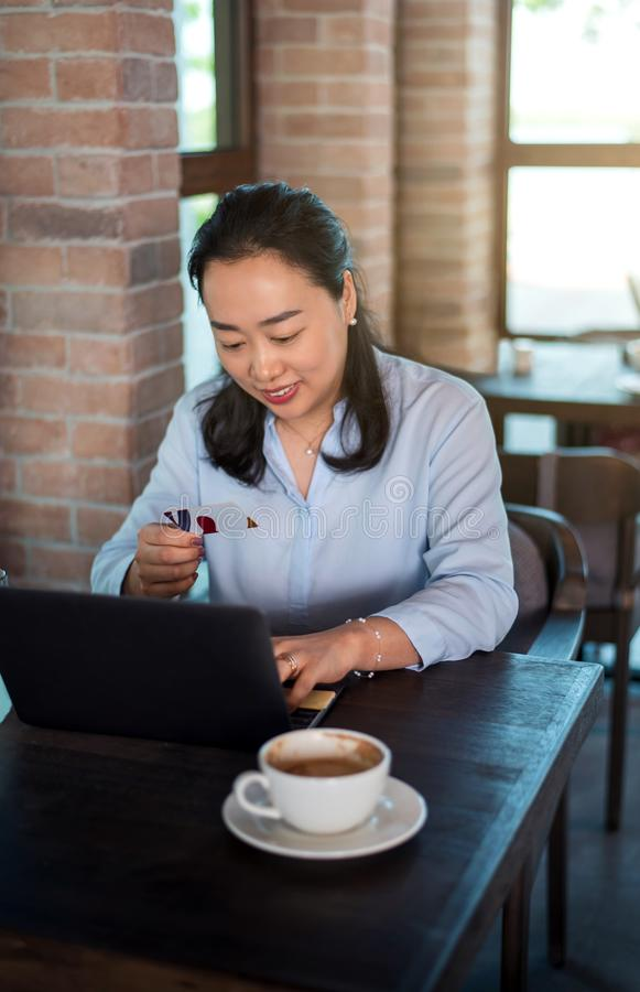 Woman online shopping and having a coffee stock photography