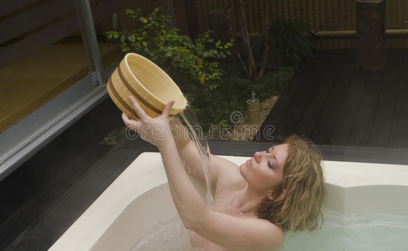 Woman in a Onsen, Japan. This woman is enjoying a relaxing day at a health spa making a hot shower in Tokyo stock images