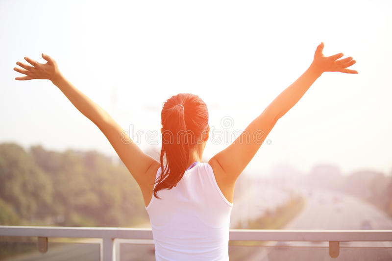 Woman open arms to the rush driveway modern city. Sporty woman stand at the pedestrian overpass open arms to the rush driveway in modern city stock photos