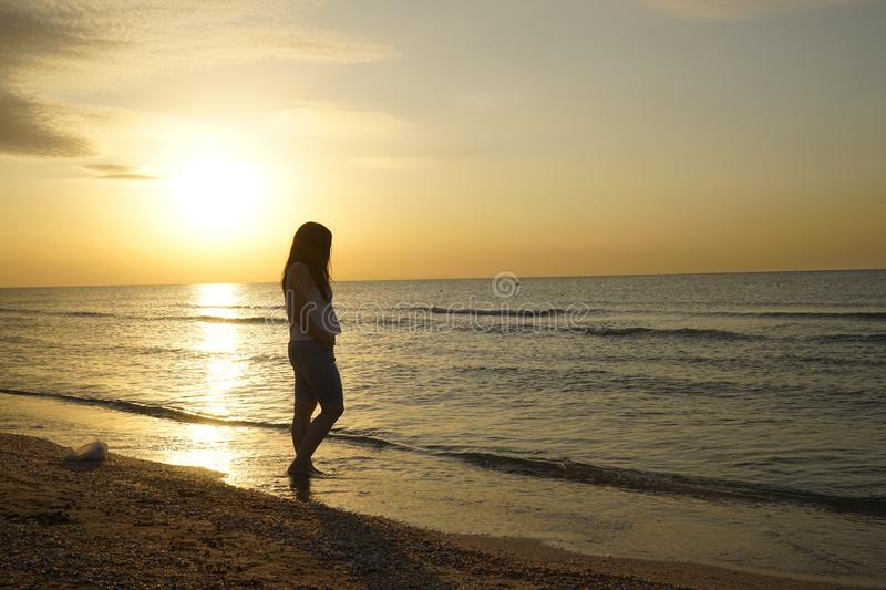 Woman open arms under the sunrise at seaside royalty free stock photography