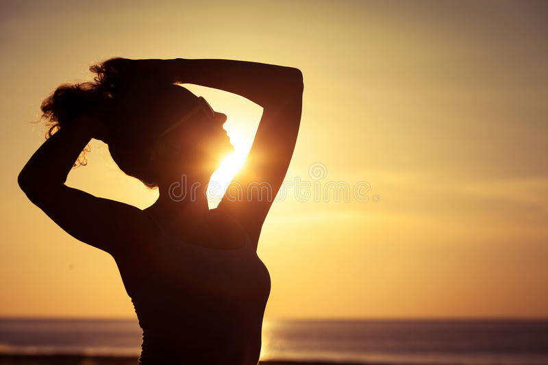 Woman open arms under the sunset. At sea royalty free stock images