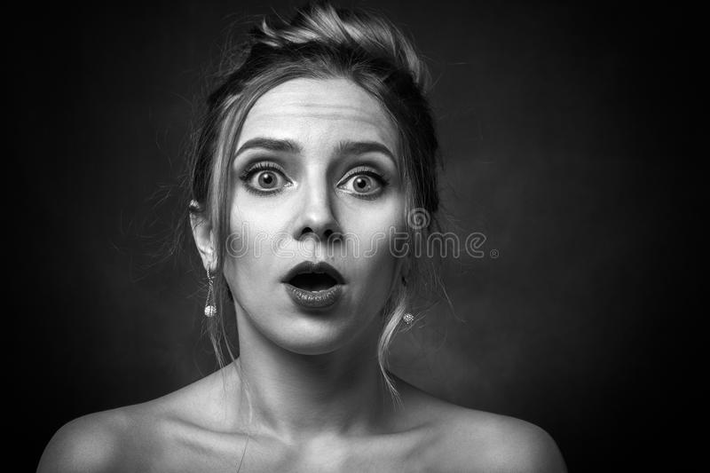 Woman open mouth. Shocked woman with open mouth on black background looking at camera, monochrome royalty free stock photography