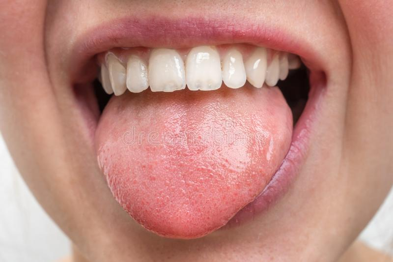 Woman with open mouth showing tongue. Young woman with open mouth showing tongue royalty free stock image