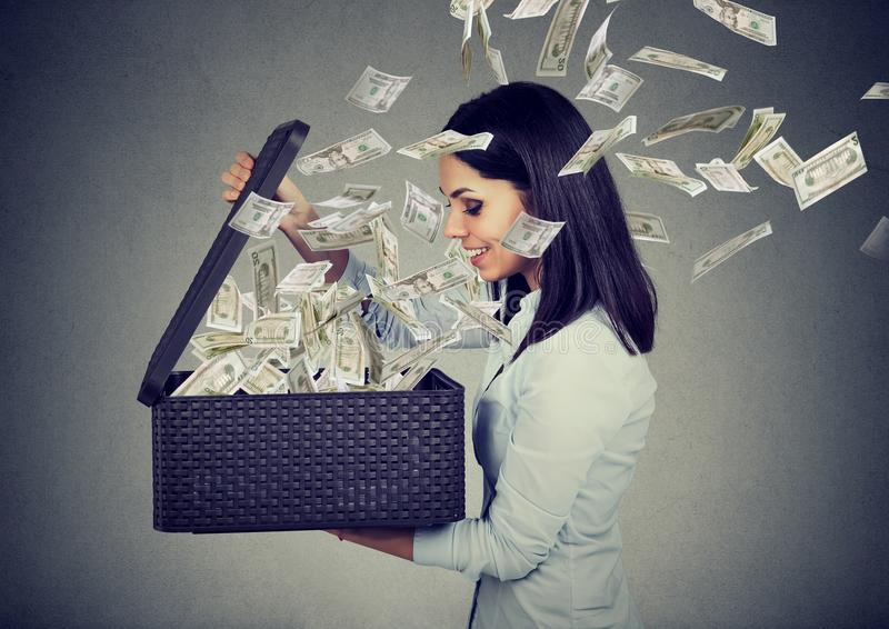 Happy woman opening a box with money flying out away royalty free stock photography