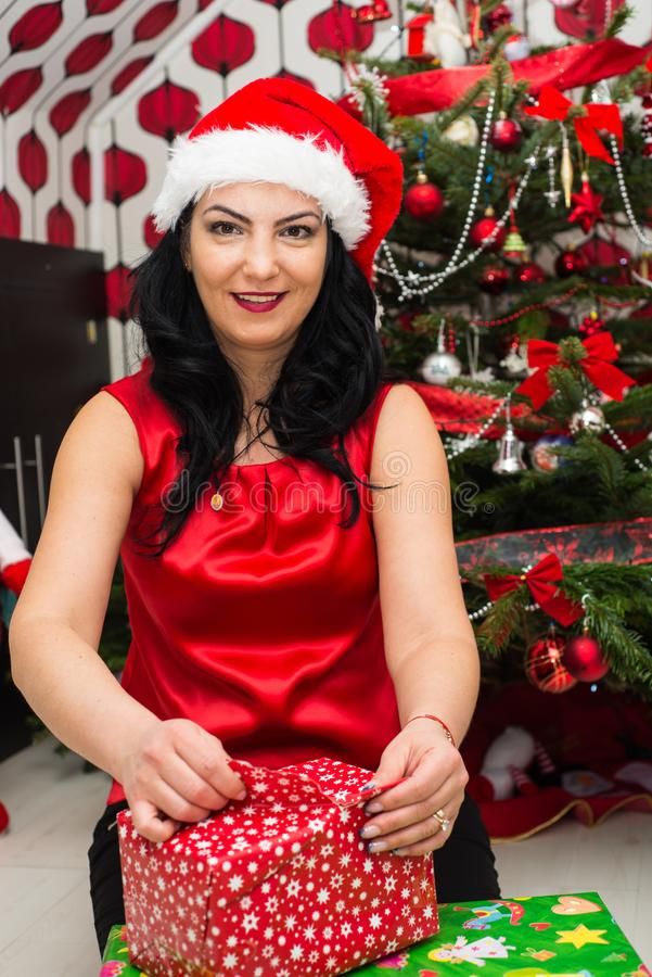 Woman opening Christmas gift. In front of Xmas decorated tree stock images