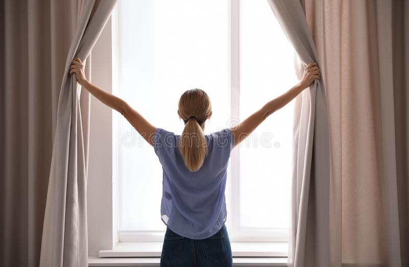 Woman opening curtains and looking out of window royalty free stock photos