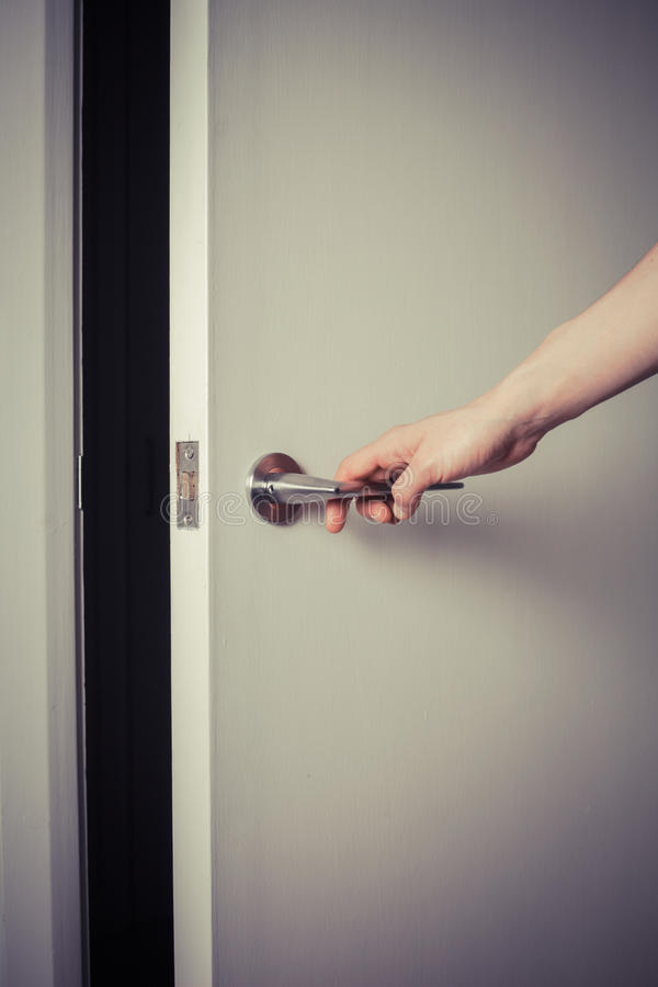Woman opening a door at night stock photo