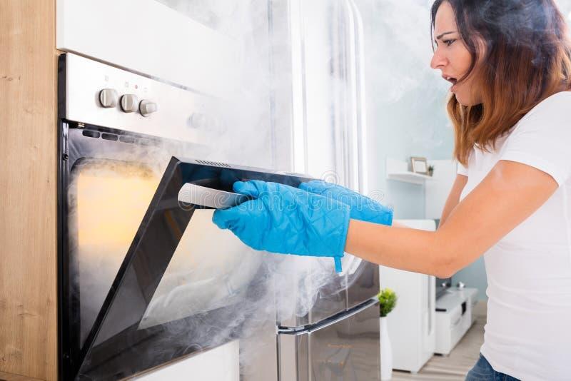 Woman Opening Door Of Oven Full Of Smoke. Young Unhappy Woman Opening Door Of Oven With Full Of Smoke stock photo