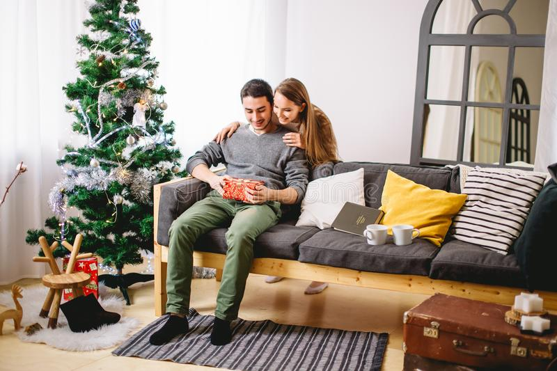 Magically surprise in box. man open christmas gift. Woman opening a gift box and smiling while her boyfriend sitting close to her on the couch with Christmas royalty free stock photos