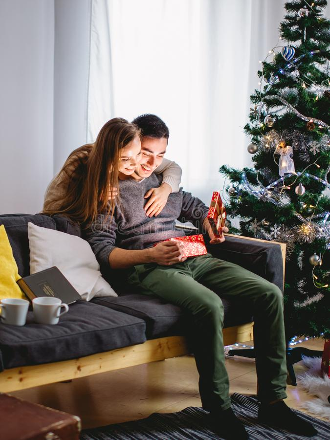 Magically surprise in box. man open christmas gift. Woman opening a gift box and smiling while her boyfriend sitting close to her on the couch with Christmas stock image