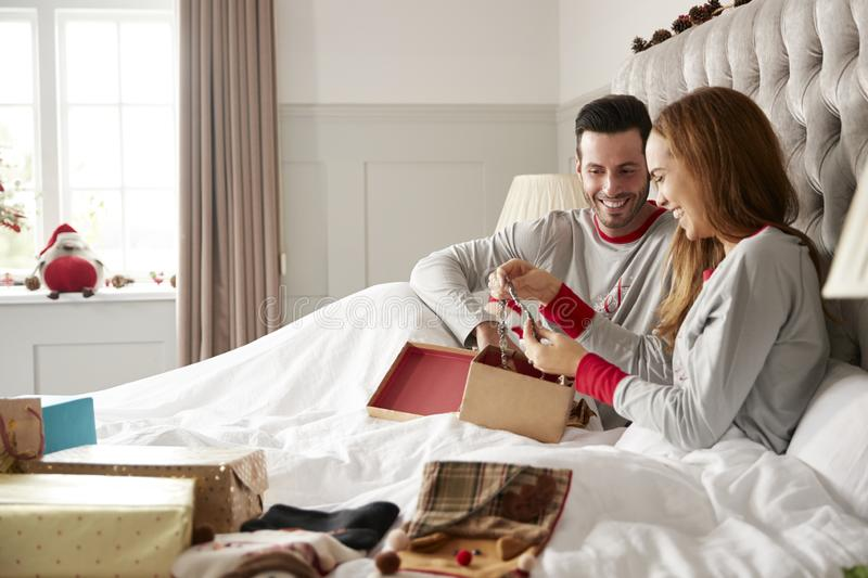 Woman Opening Gift Of Necklace In Bed At Home As Couple Exchange Presents On Christmas Day royalty free stock images