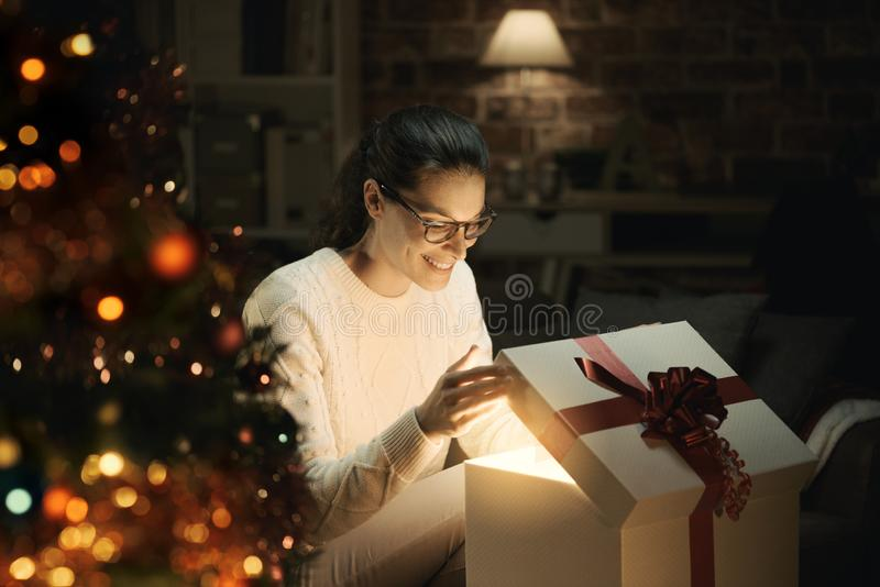 Woman opening a magical Christmas gift stock photo