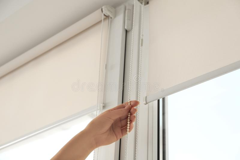 Woman opening modern roll blinds on window in room. Closeup stock photography