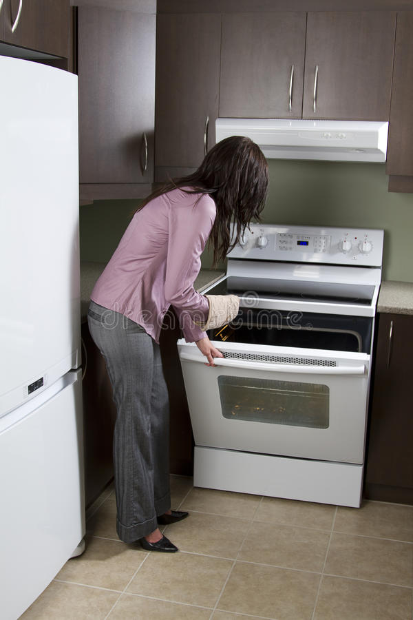 Woman opening oven. Woman standing in front of open oven with one oven mit royalty free stock photo