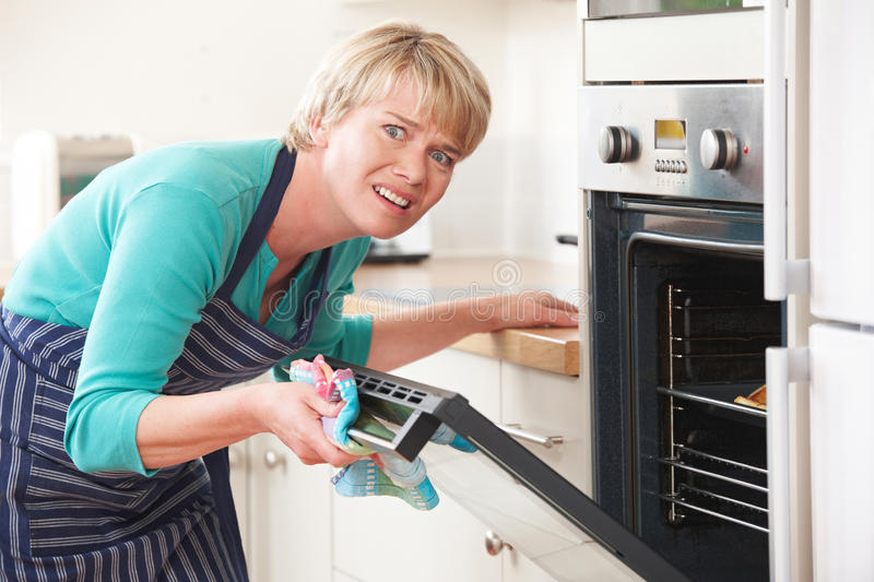 Woman Opening Oven Door And Looking Frustrated stock photo