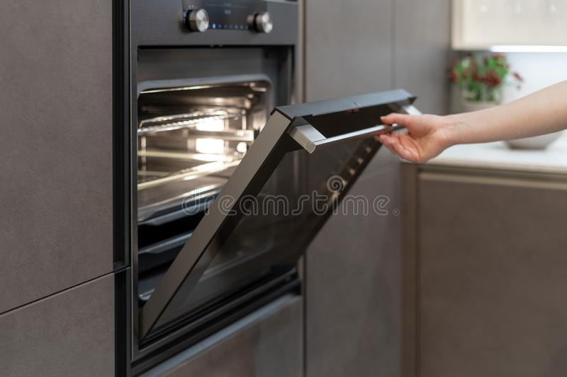 Woman opening oven with light built-in in kitchen cabinet. Woman hand opening door of new modern oven with light built-in in black kitchen cabinet stock photo