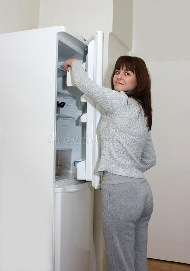 A woman opening a refrigerator stock images