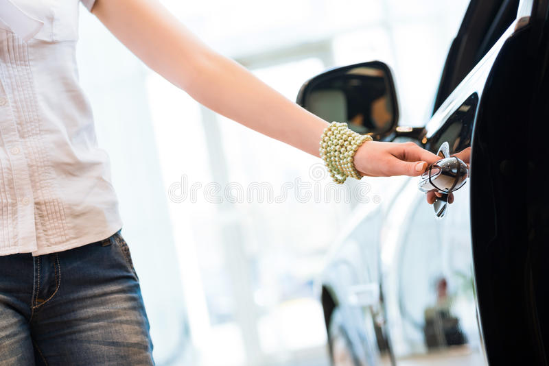 Woman opens the door to a new car. Car inspection in the showroom royalty free stock photos
