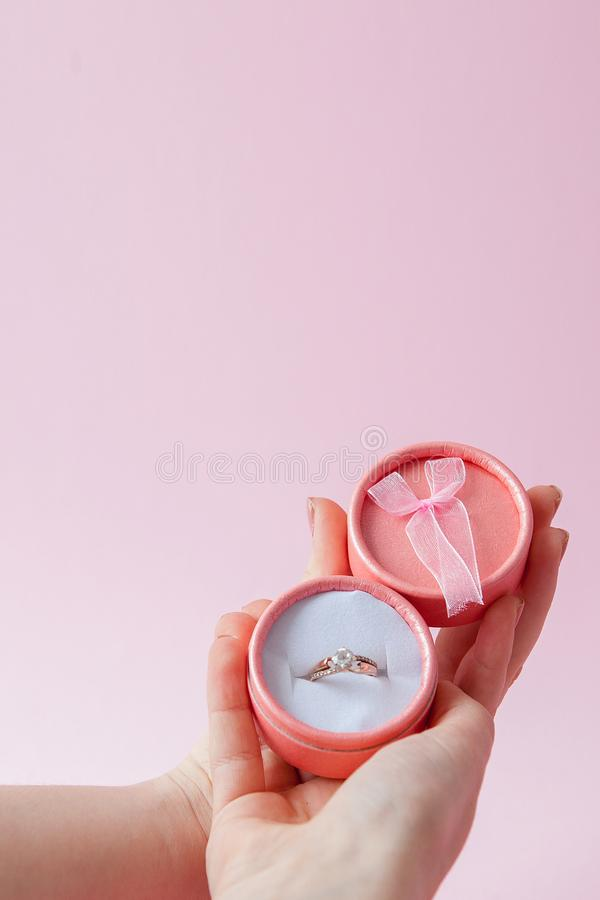 Woman opens a gift box with jewellery. Wedding ring in a box in the hands of women on a pink background stock photos