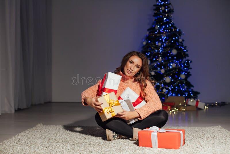 Beautiful woman opens gifts at Christmas tree holiday New Year lights garland royalty free stock image