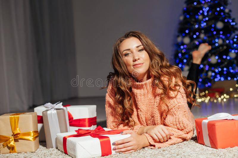 Beautiful woman opens gifts at Christmas tree holiday New Year lights garland stock photography