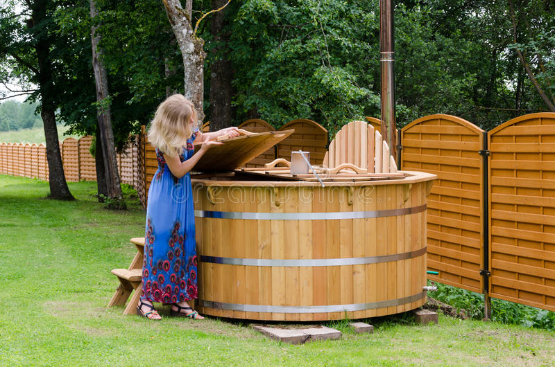 Woman opens water hot tub cover in garden. Woman opens wooden water hot tub cover in garden royalty free stock images