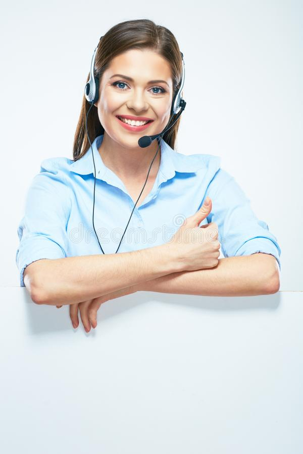 Woman operator with headset and blank sign board showing thumbs. Up. Isolated portrait of smiling help line operator royalty free stock images