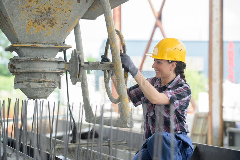 Woman operator pouring mixture in cement moulding stock photography