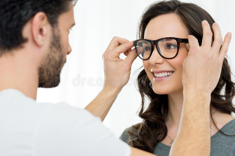 Woman at the ophthalmologist. Optician putting a new pair of eyeglasses on a patient royalty free stock photos