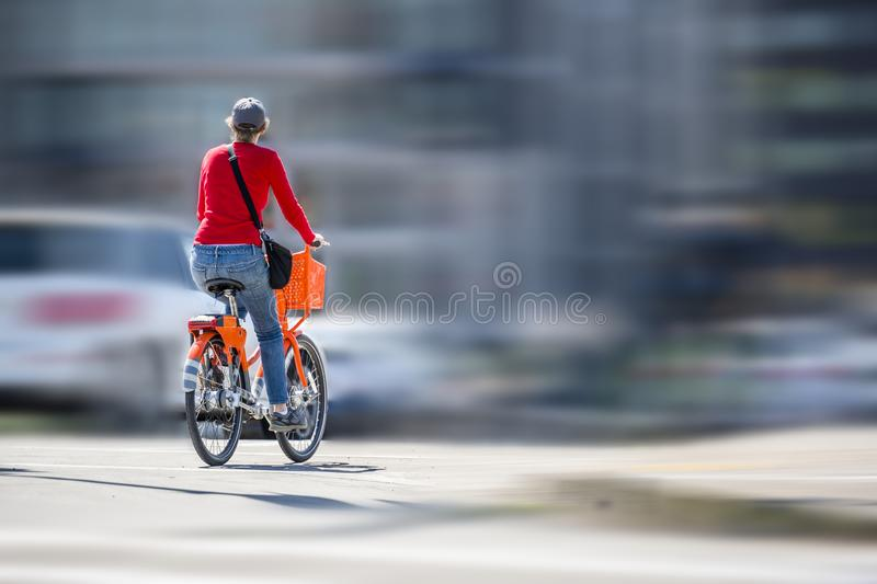 Woman on an orange bike with basket rides on bike path on the road next to other vehicles stock photography