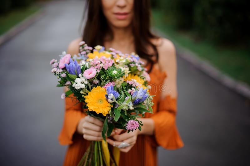 Woman in orange dress holding a colorful bouquet of flowers royalty free stock images