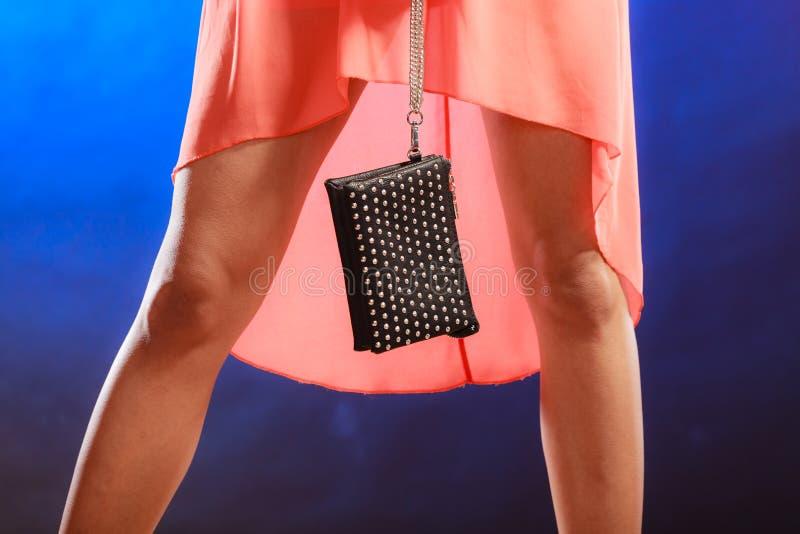 Woman in orange dress holds handbag, disco club stock images