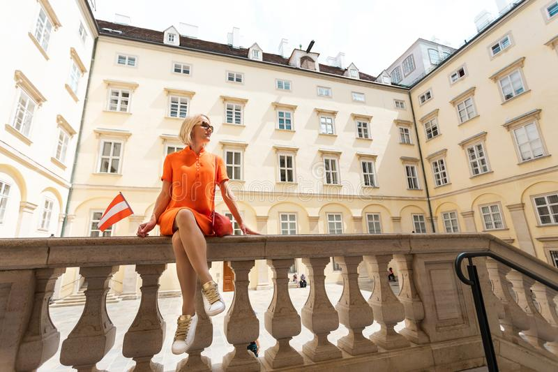 A woman in an orange dress stands in one of the courtyards of the Hofburg with the red-and-white flag of Austria in stock photo