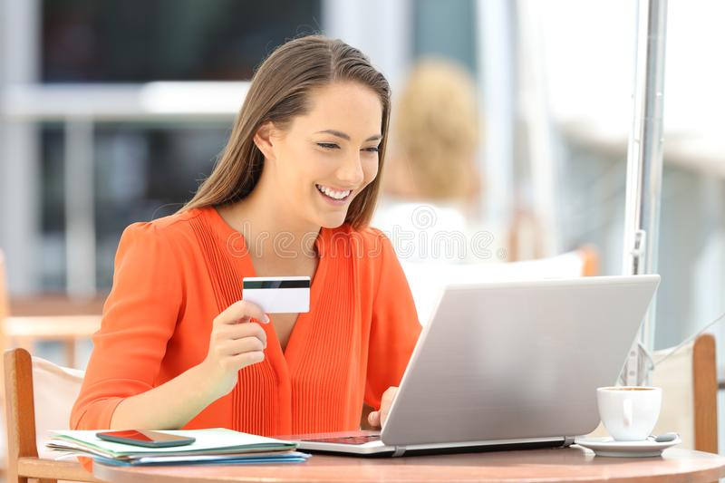Woman in orange paying on line with a credit card stock images