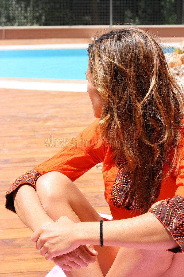 Woman in orange by the pool stock image