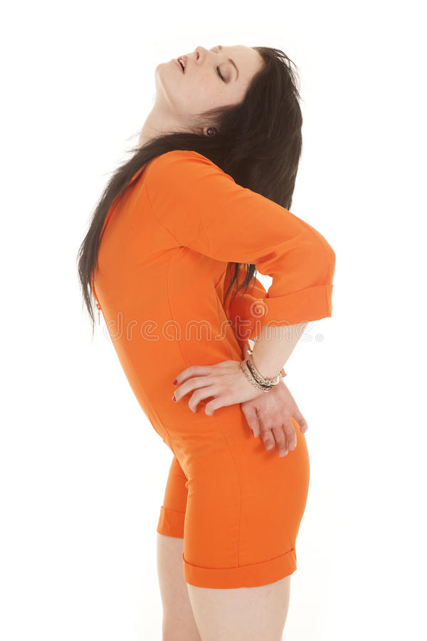 Woman orange prison handcuffs behind head back. A woman in an orange prison outfit with handcuffs stock photography