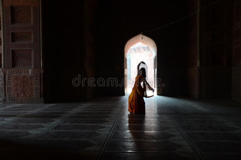 Woman in Orange and Yellow Traditional Dress Silhouette Inside Building stock image