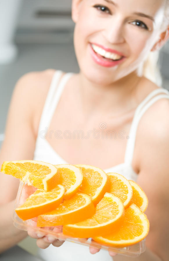 Woman with oranges. Woman with plate of orange. Focus on plate stock photography