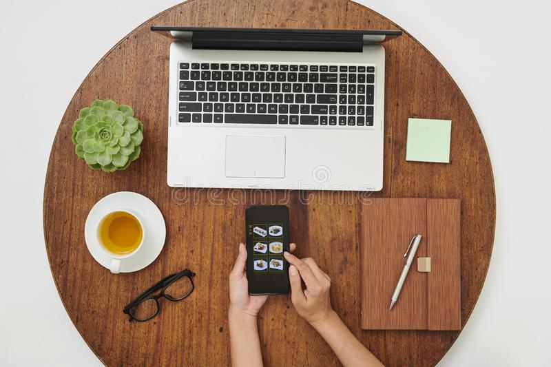 Woman order a takeaway. Close-up of woman sitting at wooden table with laptop and notepad and order takeaway online in her mobile phone she decided to take a royalty free stock image