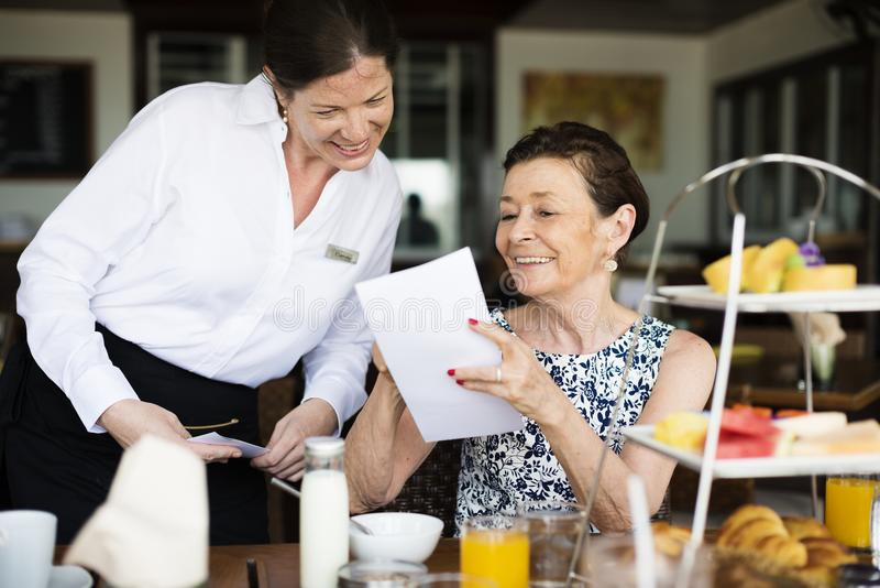 Woman ordering from a menu at restaurant royalty free stock photo