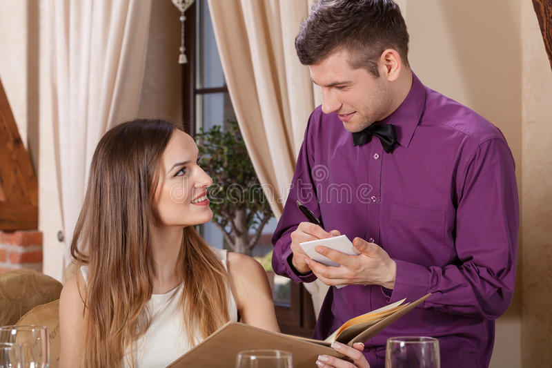 Woman ordering in a restaurant. Waiter and women ordering meal in a restaurant stock images
