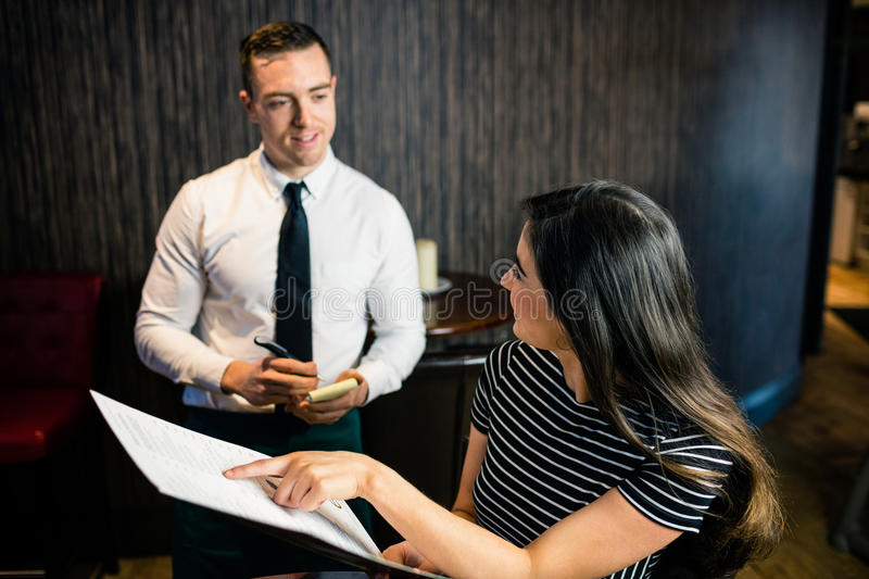 Woman ordering to waiter from the menu. In a restaurant stock photo