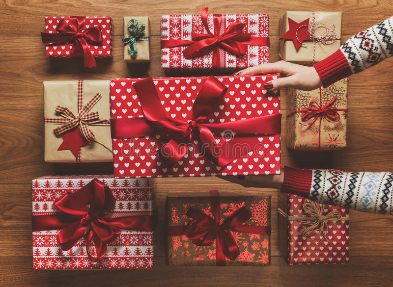 Woman organising beautifully wrapped vintage christmas presents on wooden background, image with haze royalty free stock image