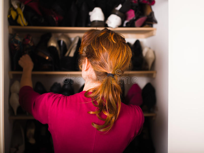 Woman organizing her shoes. A young woman is organizing her shoe cupboard at home stock photography