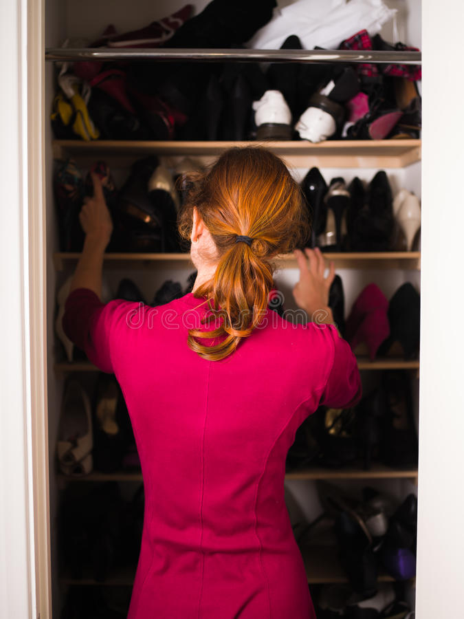 Woman organizing her shoes. A young woman is organizing her shoe cupboard at home stock photos